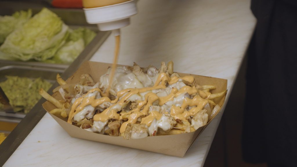 Drizzling creamy sauce on funky fries