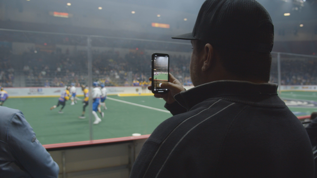 Shawn walchef uses his cell phone to record a san diego seals game at pechenga arena