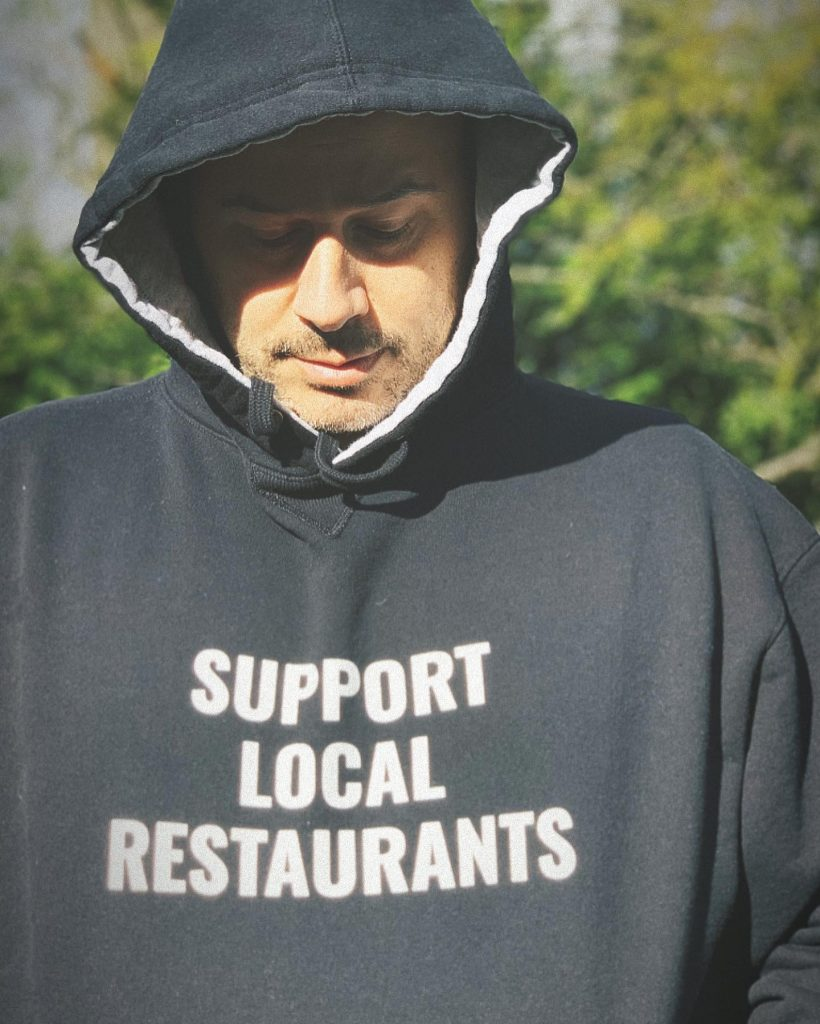 Kyle inserra wearing a support local restaurants hoodie