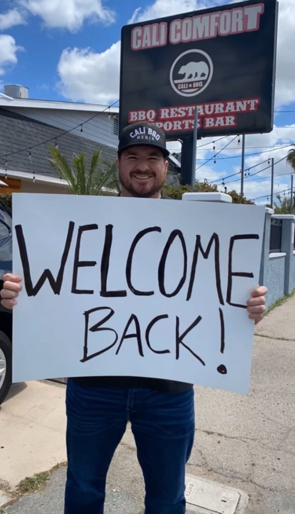 Shawn walchef holding welcome back sign at cali bbq in spring valley