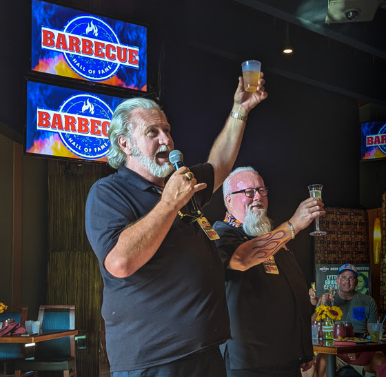 Myron mixon gives a toast with dr. Bbq ray lampe at the 2021 barbecue hall of fame induction ceremony at the american royal world series of bbq
